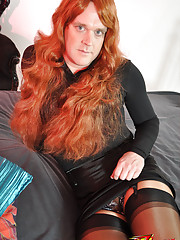 Fiery red haired TGirl posing on her big bed and looking sensual